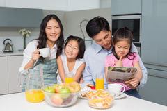 Family of four enjoying healthy breakfast in kitchen. Portrait of a happy family of four enjoying healthy breakfast in the kitchen at home royalty free stock image