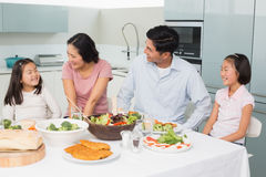 Family of four enjoying healthy meal in kitchen Stock Photography