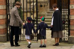 Family of four entering old school gates Stock Images