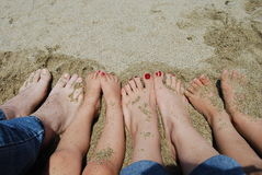 Family feet on the beach. A family of four feet on the beach in the sand stock image