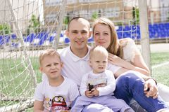 A family of four on a football field. Bright sunny summer day stock images