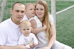 A family of four on a football field. Bright sunny summer day Stock Photos