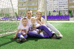 A family of four on a football field. Bright sunny summer day royalty free stock photo