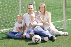 A family of four on a football field. Bright sunny summer day Royalty Free Stock Images