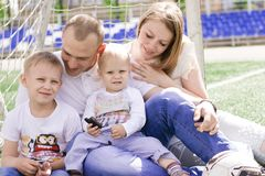 A family of four on a football field. Bright sunny summer day Royalty Free Stock Photos