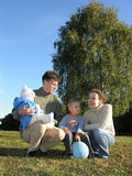 Family of four on grass. Blue sky autumn royalty free stock photos