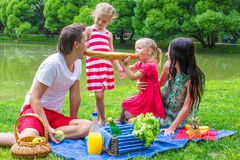 Family of four have picnic in the park on summer Stock Photo