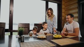 Family of four having Breakfast in his kitchen with large Windows. People are smiling, mother kissing and hugging stock footage