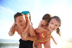 Family of four having fun at the beach. Stock Photo