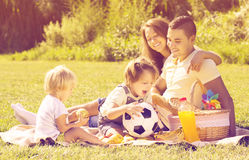 Family of four having picnic. Happy young family of four having picnic at meadow. Focus on man stock photo