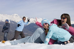 Family of four having snow ball fight in snow field, smiling, mountain range in background royalty free stock image