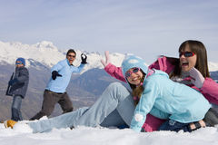 Family of four having snow ball fight in snow field, smiling, mountain range in background Royalty Free Stock Photography