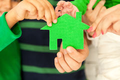 Family of four holding green house in hands Stock Image