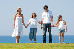 Family of four holding hands stock image