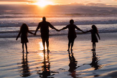 Family of four holding hands silhouettes. Standing on beach with sunset in background. No faces Royalty Free Stock Photography
