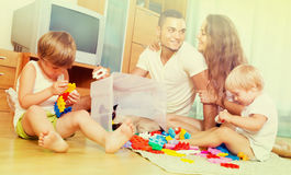 Family of four at home with toys Royalty Free Stock Image