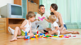 Family of four at home with toys Stock Images
