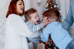 A family of four hugging in front of the christmas tree. love, happiness and big family concept stock image