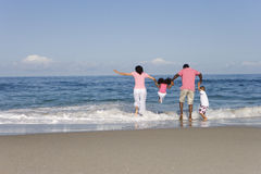 Family of four jumping waves, rear view Stock Photos