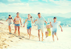 Family with four kids happily running on beach Royalty Free Stock Photos