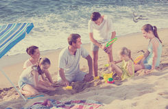 Family with four kids relaxing on beach Stock Photos