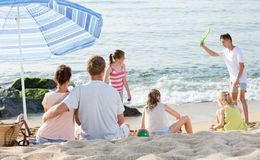 Family with four kids relaxing on beach Stock Image