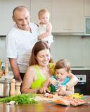 Family of four in the kitchen preparing seafood Royalty Free Stock Image