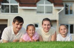 Family from four lies on grass against house Stock Image