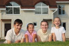 Family from four lies on grass against house Royalty Free Stock Photo