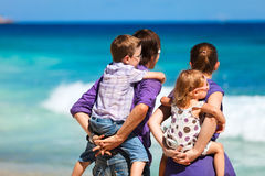 Family of four looking to ocean Stock Photos