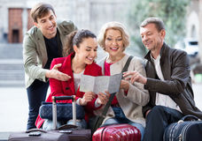 Family of four with luggage checking direction in map Royalty Free Stock Photography