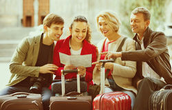 Family of four with luggage checking direction in map Stock Photos