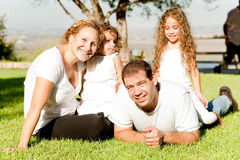 Family of four lying in grass Royalty Free Stock Photo