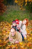 Family of four lying on the grass in the form of a pyramid.  Stock Photography