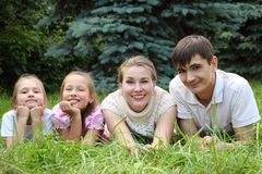 Family of four lying on grass and looks Royalty Free Stock Images