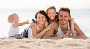Family of four lying together on beach vacation Royalty Free Stock Photography