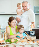 Family of four making dumplings with red fish (dumplings) in a h Photographie stock libre de droits