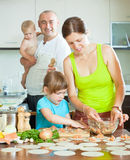 Family of four making russian dumplings (pelmeni)  together Royalty Free Stock Images