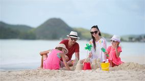 Family of four making sand castle at tropical white beach. Family making sand castle at tropical beach stock footage