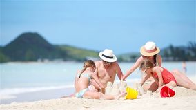 Family of four making sand castle at tropical white beach stock video footage