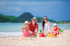 Family of four making sand castle at tropical white beach. Family making sand castle at tropical beach Stock Photo