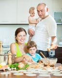 Family of four making small dumplings with fish (dumplings) in a Stock Photo