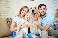 Family of four. Modern family and their cute pet resting at home Royalty Free Stock Photo