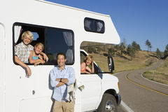 Family of four with motor home, man with map by son and daughter (8-12), mother looking out of window, smiling, portrait. Family of four with motor home, men royalty free stock image