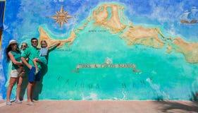 Family of four near big map of Caribbean island Royalty Free Stock Photos
