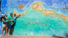 Family of four near big map of Caribbean island Stock Images