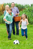 Family of four outdoor playing football Stock Photography