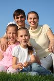 Family of four outdoor in summer sits on grass royalty free stock photo