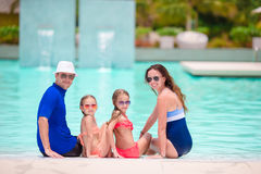 Family of four in outdoor swimming pool Royalty Free Stock Photos