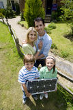 Family of four outdoors with solar panel, portrait, elevated view Stock Photo